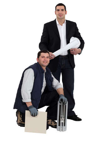 tile cutter: Portrait of an engineer and a workman holding a tile and a ceramic tile cutter