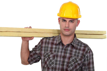 Carpenter carrying planks of wood photo