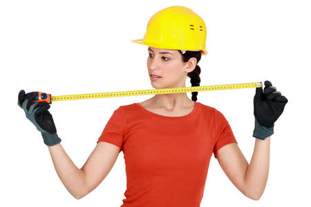 tradeswoman: Tradeswoman using a measuring tape Stock Photo