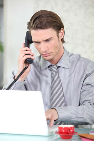Young businessman on the phone while using his laptop photo