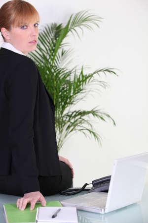 exceeded: Exceeded businesswoman sitting on her desk