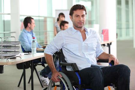 persona en silla de ruedas: Hombre que usa una silla de ruedas en un entorno de oficina