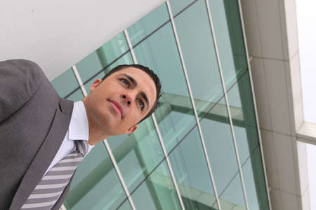 Young executive standing outside a modern office building Stock Photo - 11825499