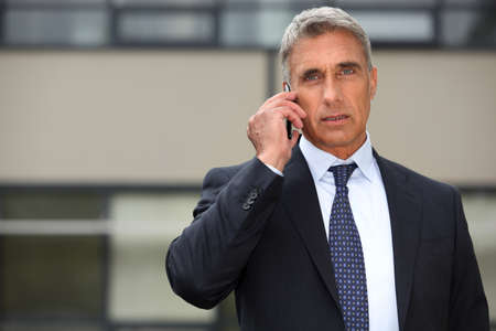 talking businessman: Mature businessman using a cell phone Stock Photo