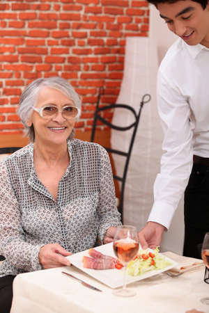 Young waiter serving an older woman in a restaurant photo