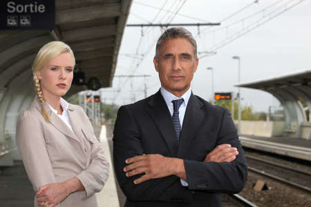 forfeiture: a blonde woman and a mature man well dressed in a train station Stock Photo