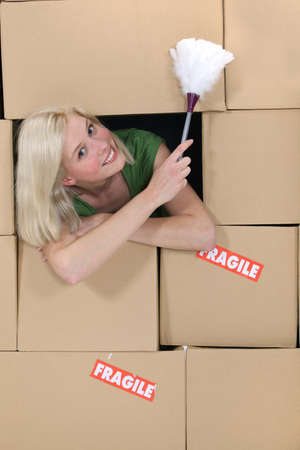 moving in: radiant blonde amid cardboard boxes holding feather duster