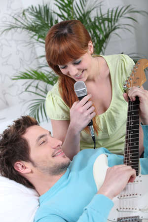 Woman beat guitar: Young couple with a guitar and a microphone Kho ảnh