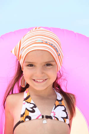 bandana girl: Little girl at the beach with inflatable rubber ring