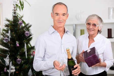 65 years old: Elderly couple celebrating together at Christmas Stock Photo