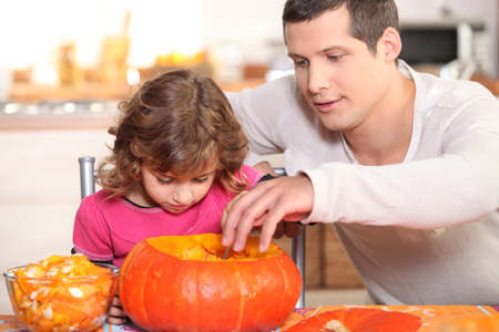 Father and daughter preparing pumpkin photo