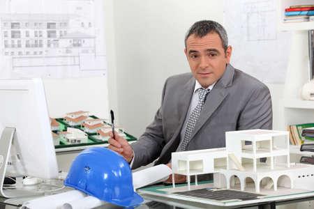 topógrafo: Arquitecto en la oficina rodeado de los planes de