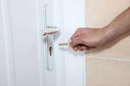doorlock: Man putting key in the lock of a door Stock Photo
