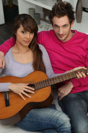 Woman beat guitar: couple playing guitar at home