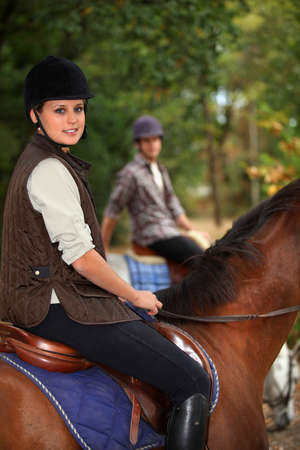 Man training blond teenager to horse ride photo