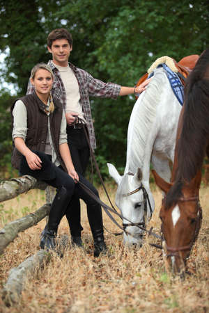 Young couple out with horses photo