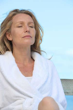 destress: Woman in a bathrobe relaxing in the sunshine