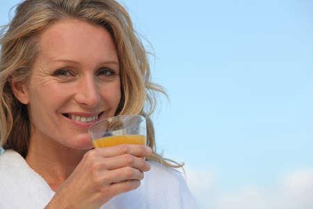 Closeup of a woman in a bathrobe drinking orange juice outdoors photo