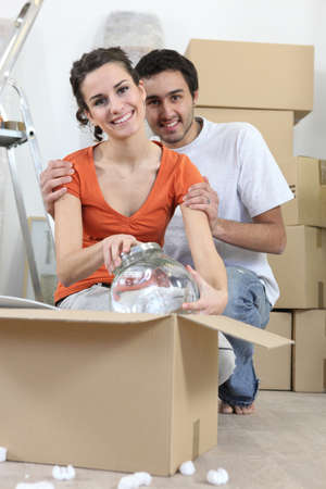 Couple unpacking fragile box photo