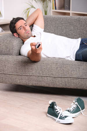 t off: Man relaxing on sofa watching television