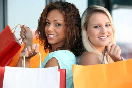 bargain: two girls doing shopping Stock Photo