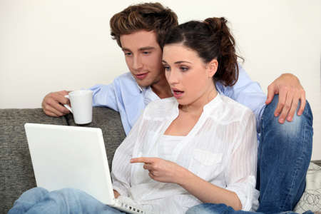 Shocked couple looking at laptop photo