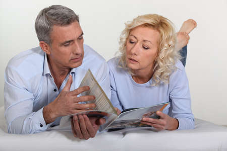 50 55 years: Couple looking at a catalogue