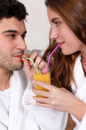 oj: Couple sharing a glass of orange juice Stock Photo