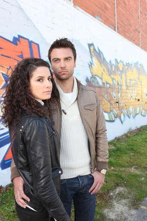 beau jeune homme: La mode jeune couple se tenait près mur Banque d'images