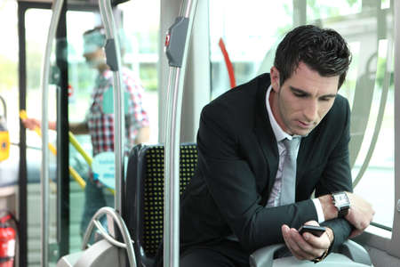 man texting in a bus photo