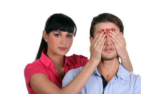 woman putting her hands on man eyes photo