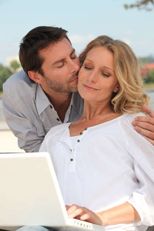 tenderly: Man kissing a woman tenderly on the cheek Stock Photo