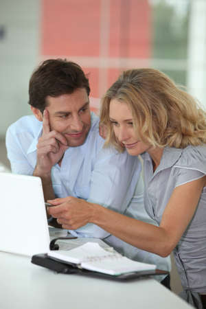 35 40 years: Husband looking at wife on laptop. Stock Photo