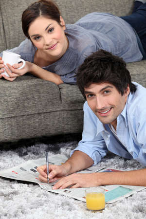 mass media: couple reading newspaper at home Stock Photo