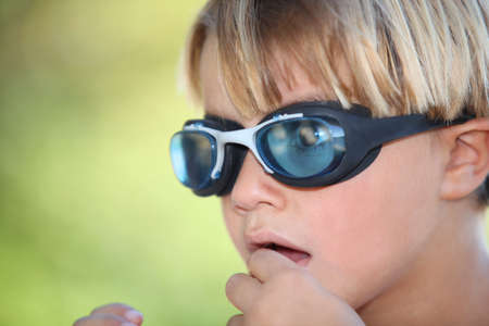 Nervous young boy wearing swimming goggles photo
