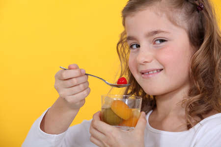 Cute little girl eating salad of fruits photo