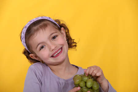 Young girl with a bunch of grapes Stock Photo - 11823365