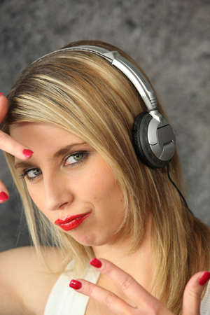 Woman wearing headphones making youthful gesture photo