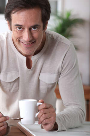45 55 years: Man smiling with a cup of tea.