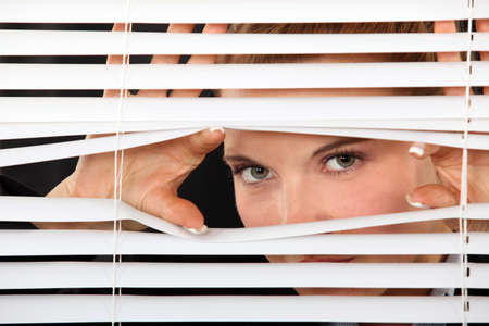 window coverings: Woman peering through blinds