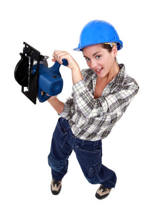 A female manual worker with a circular saw. photo