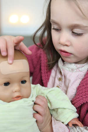 Little girl putting a plaster on her baby doll photo