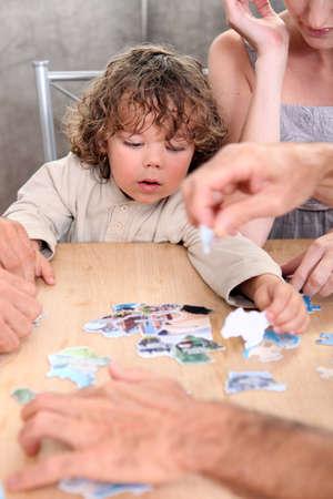 2 to 3 years: Little boy giocare con le immagini a un tavolo