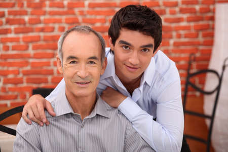 a teenager and his grandfather posing in a restaurant photo