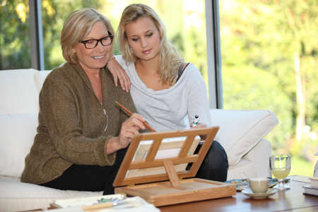 Woman showing her granddaughter how to paint photo