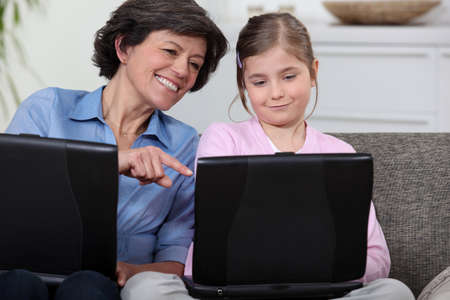 Mother and daughter son on sofa with their own laptops photo