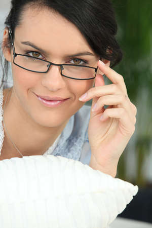 self contained: beautiful young woman watching over her glasses Stock Photo