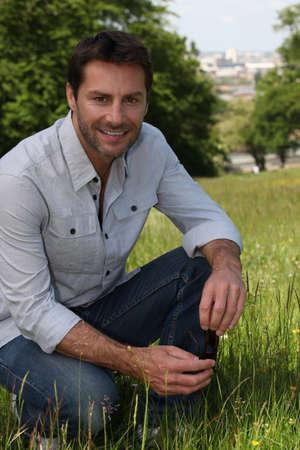 arrodillarse: El hombre de rodillas sobre la hierba