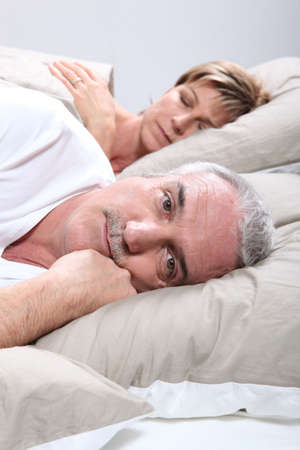 hombre preocupado: un hombre est� despierto cuando su esposa est� durmiendo