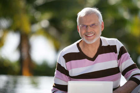 Senior man with a laptop in the sunshine Stock Photo - 11823391